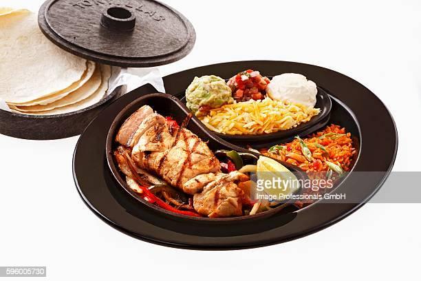 Chicken fajita with accompaniments and tortillas