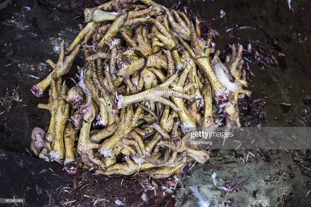 Chicken feet sit stacked in a pile at a butcher's stall in the New Market area of Kolkata, West Bengal, India, on Friday, Nov. 1, 2013. Indian stocks fell for the first time in six days, led by technology and consumer companies, after benchmark indexes climbed to records in a holiday trading session on Nov. 3. Photographer: Sanjit Das/Bloomberg via Getty Images