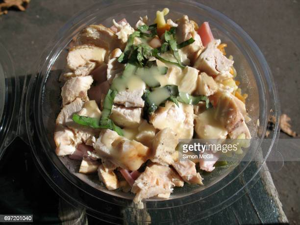 Chicken, ham and pasta in a plastic container on a man's lap in a park