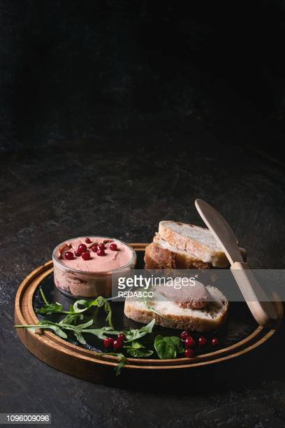 Chicken homemade liver paste or pate with sliced whole grain bread wood knife cranberries green salad served in glass jar on wooden slate serving...