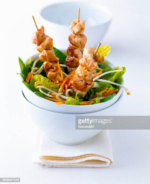 Chicken kebab in a bowl of salad on white ground