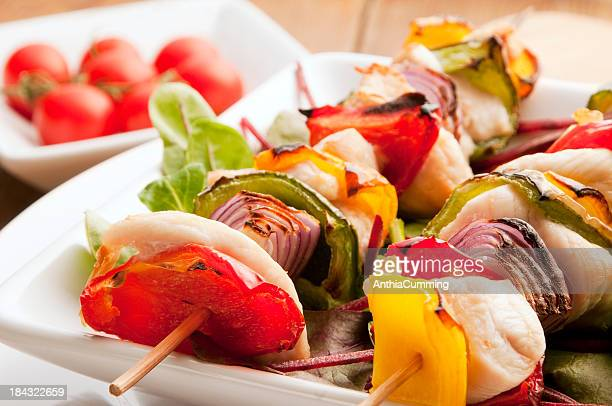 Chicken kebab skewer with peppers and onion on white plate