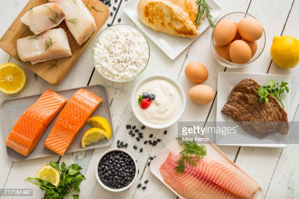 chicken meat, fish, cottage cheese, yogurt and eggs on white table - raw food stock pictures, royalty-free photos & images