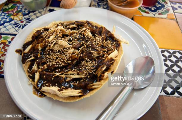 chicken mole tostada on a white plate on a tiled table top - mole sauce stock pictures, royalty-free photos & images