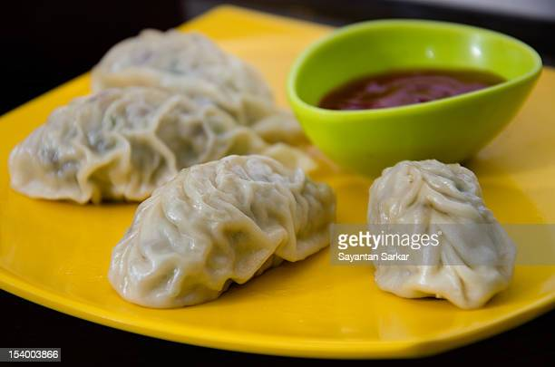 Chicken Momo with spicy sauce in yellow plate