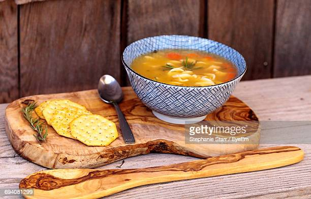 Chicken Noodle Soup In Bowl With Crackers On Cutting Board Over Table