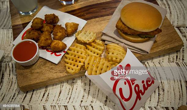 Chicken nuggets french fries and a fried chicken sandwich are arranged for a photograph during an event ahead of the grand opening for a ChickfilA...