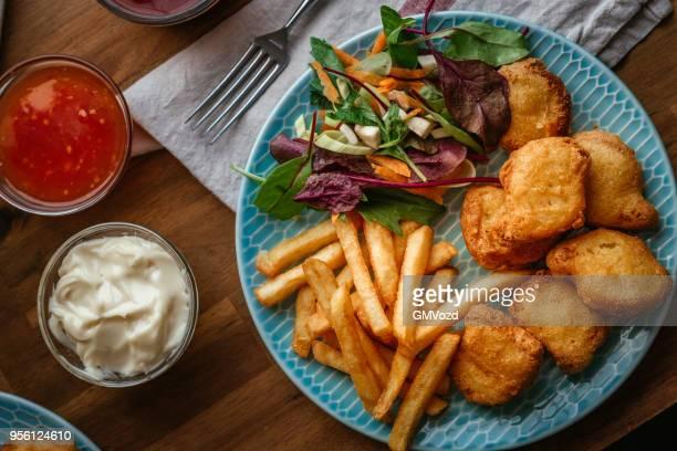 Nuggets de pollo con papas fritas y ensalada verde