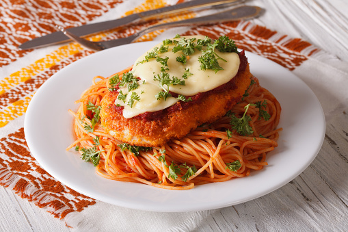 Chicken Parmigiana and pasta with tomatoes close-up 609044752