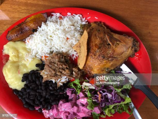 Chicken, rice, beans, salad, and plantain on a red plate