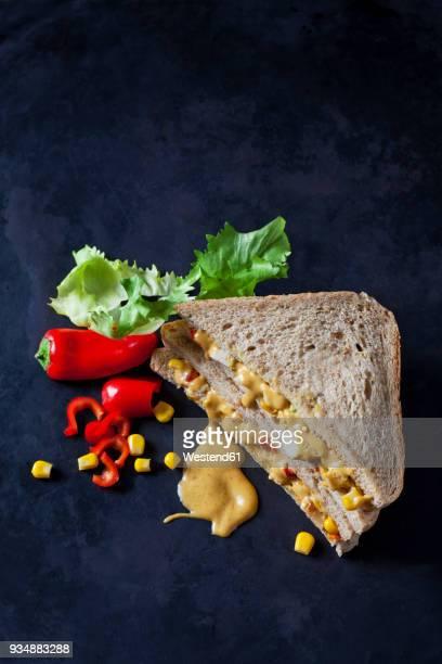 chicken sandwich with corn, pepperoni and curry sauce on dark ground - pimientos fotografías e imágenes de stock