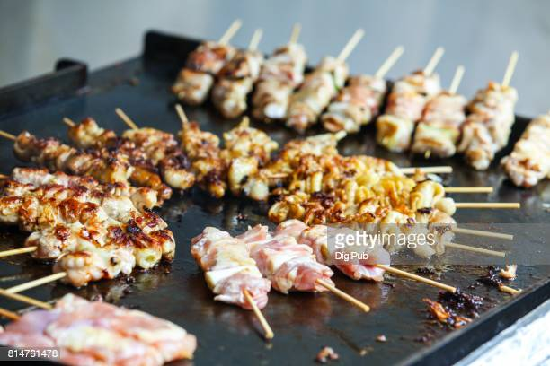 Chicken skewers being cooked on teppan hot plate
