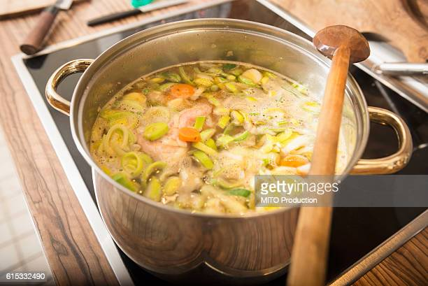 Chicken soup boiling with leek and carrot in a pot on stove, Munich, Bavaria, Germany