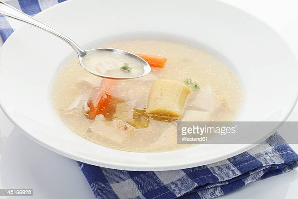 Chicken soup in plate with spoon on napkin, close up