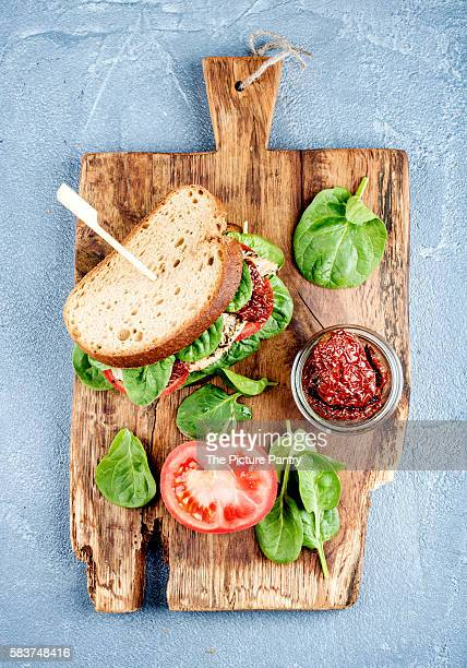 Chicken, sun-dried tomato and spinach sandwich with spicy sauce on rustic wooden board over grey concrete textured background