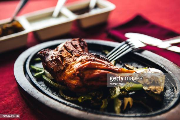 Chicken tandoori on a cast iron plate with chutney. North Indian food