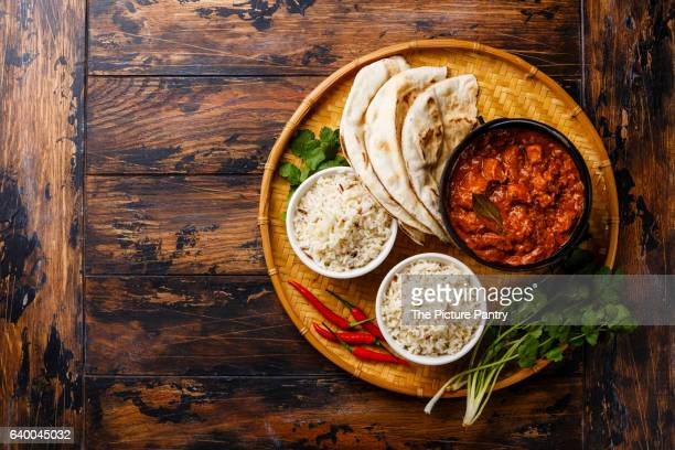 Chicken tikka masala spicy curry meat food in cast iron pot with rice and fresh naan bread on wooden background copy space