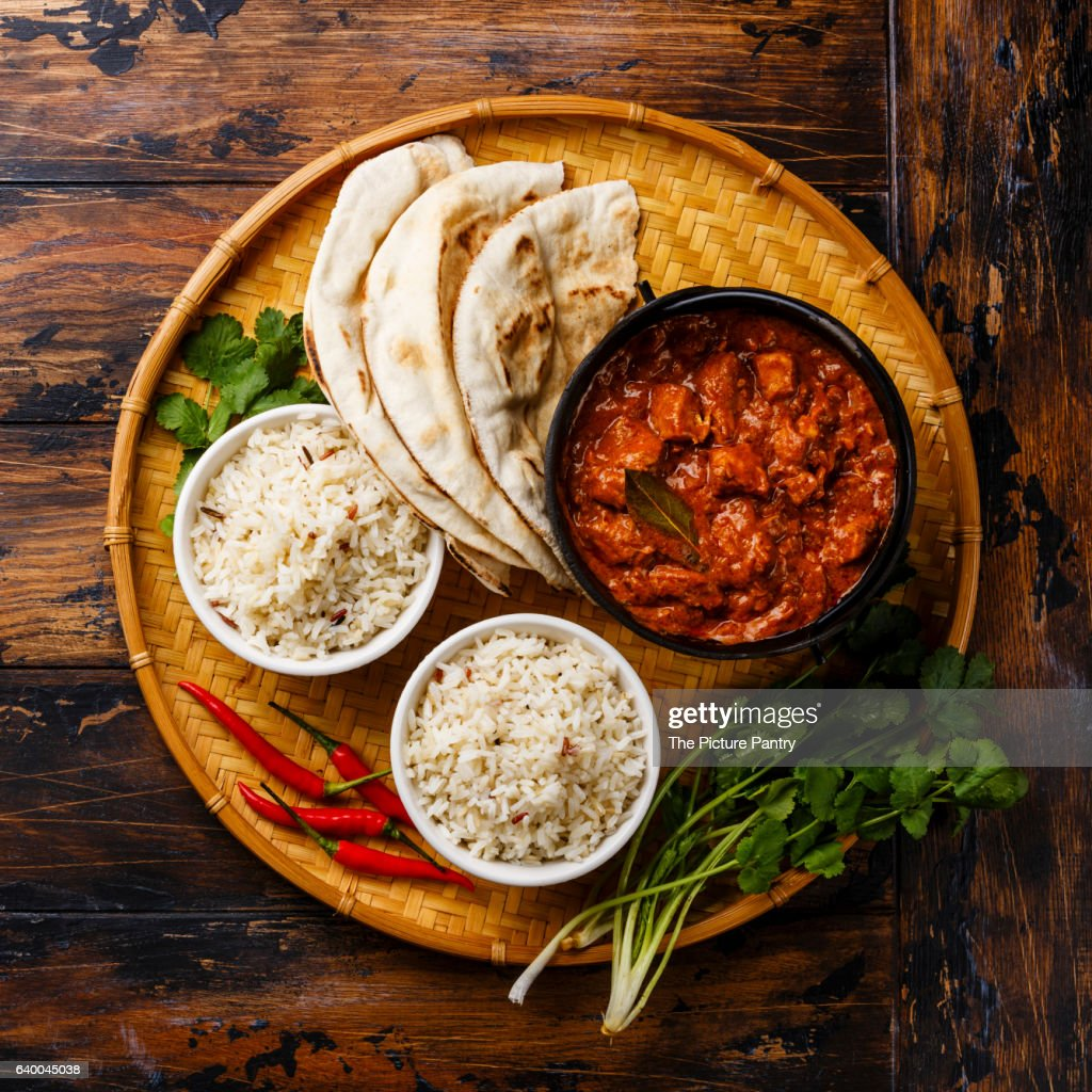 Chicken tikka masala spicy curry meat food in cast iron pot with rice and fresh naan bread on wooden background : Stock Photo