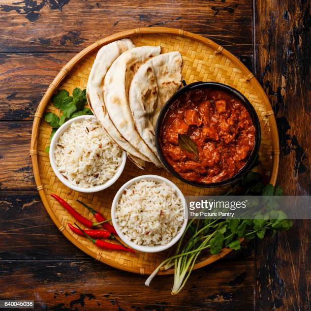 Chicken tikka masala spicy curry meat food in cast iron pot with rice and fresh naan bread on wooden background