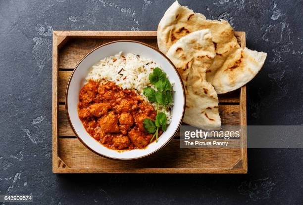 Chicken tikka masala spicy curry meat food with rice and fresh naan bread in wooden tray on black stone background