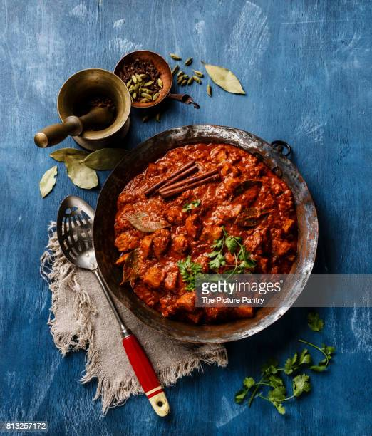 chicken tikka masala spicy indian curry in a copper pan on blue wooden background - chicken masala stock photos and pictures