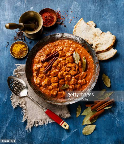 Chicken tikka masala spicy Indian curry in a copper pan on blue wooden background