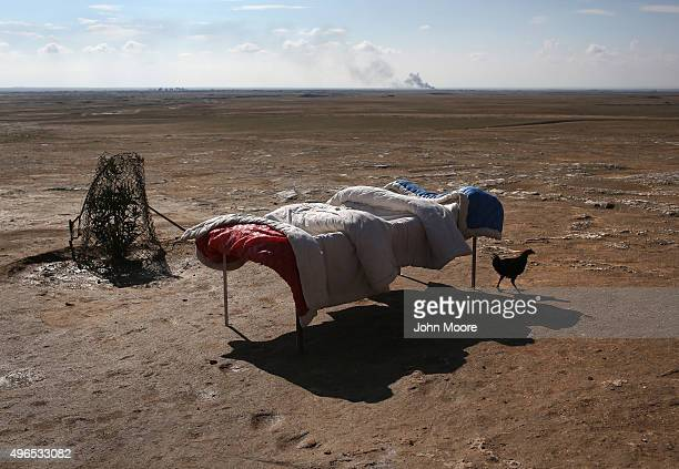 A chicken walks past a bed airing out after the village was liberated from ISIL on November 10 2015 near the ISILheld town of Hole in the autonomous...