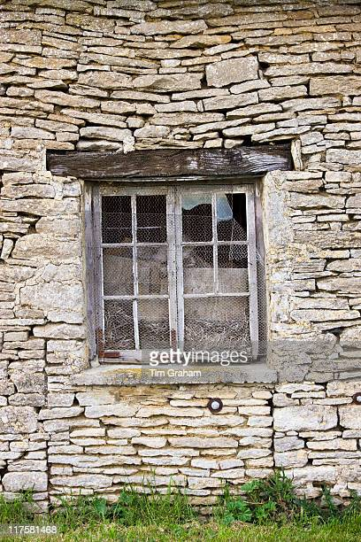 Chicken wire on broken window of old derelict subsiding stone barn Kelmscott The Cotswolds Gloucestershire UK