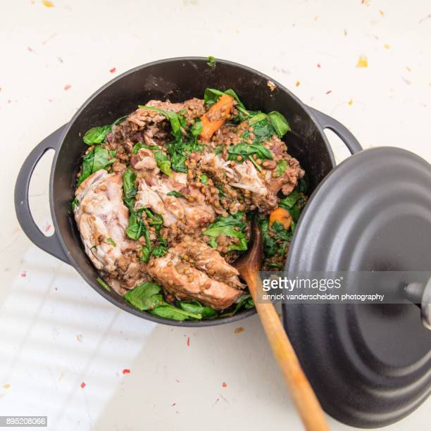 Chicken with lentils and spinach in cast iron casserole.