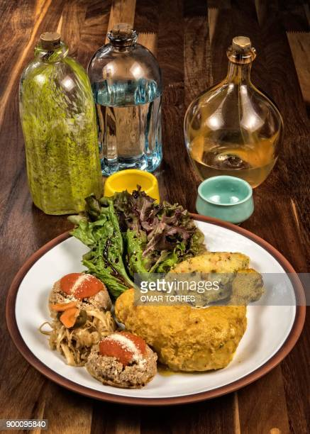 Chicken Zandunga baked in a clay pot with mustard dressing is served with lettuce salad mashed potatos and garnachas a dish made with corn tortillas...