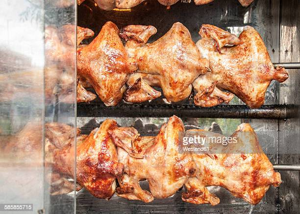 Chickens roasting on a grill