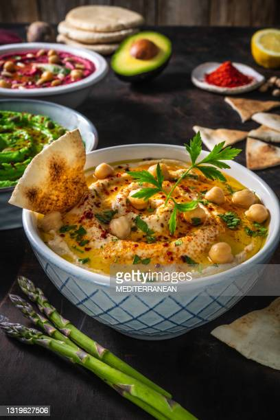 chickpea hummus bowl closeup with pita flatbread dipping and asparagus sticks on dark wood - lebanon country stock pictures, royalty-free photos & images