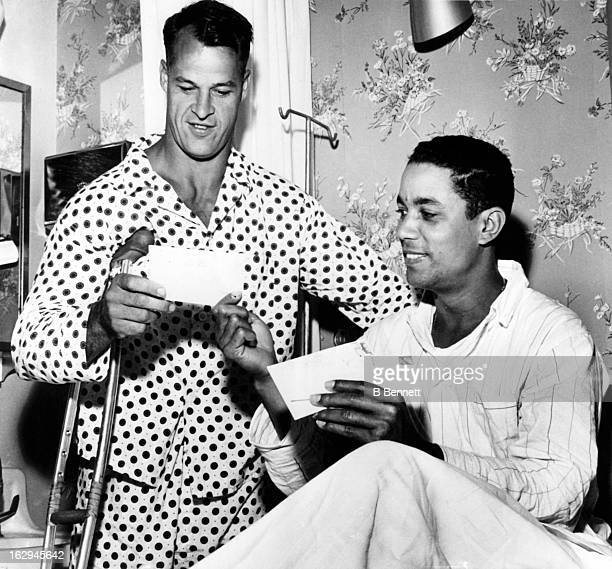 Chico Fernandez of the Detroit Tigers shares some of his fan mail with Gordie Howe of the Detroit Red Wings as they recuperate in the Detroit...