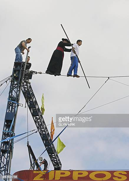 Chico Marinhos a high wire walker is followed by local priest Father Jerome Lloyd as they walk across a wire suspended 80 feet above the ground in...