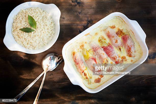 Chicory gratin wrapped in ham with béchamel sauce and rice on a plate