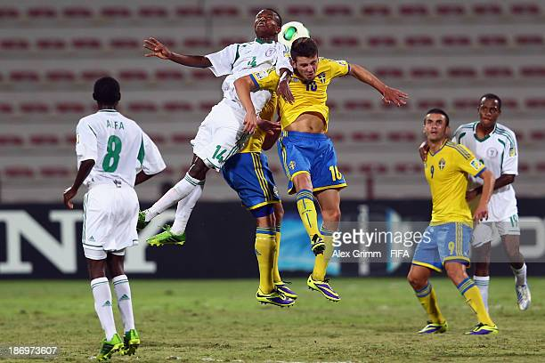 Chidiebere Nwakali of Nigeria jumps for a header with Erdal Rakip of Sweden during the FIFA U17 World Cup UAE 2013 Semi Final match between Sweden...
