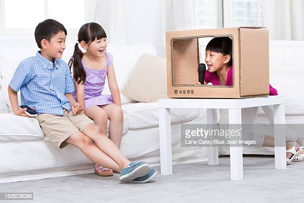 Chidren and a handmade toy TV