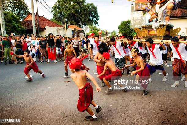 chidren fighting an ogoh-ogoh figure during the nyepi ngrupuk parade - melasti stock photos and pictures