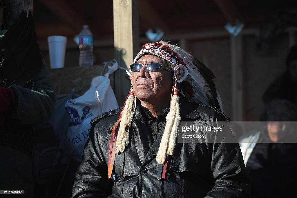 Chief Arvol Looking Horse of the Lakota/Dakota/Nakota Nation listens to speakers during an interfaith ceremony at Oceti Sakowin Camp on the edge of the Standing Rock Sioux Reservation on December 4, 2016 outside Cannon Ball, North Dakota. Native Americans and activists from around the country have been gathering at the camp for several months trying to halt the construction of the Dakota Access Pipeline. Today the US Army Corps of Engineers announced that it will not grant an easement for the pipeline to cross under a lake on the Sioux Tribes Standing Rock reservation, ending the months-long standoff. The proposed 1,172-mile-long pipeline would transport oil from the North Dakota Bakken region through South Dakota, Iowa and into Illinois.