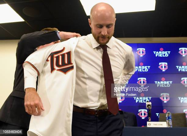 Chief Baseball Officer Derek Falvey of the Minnesota Twins helps new manager Rocco Baldelli into his jersey as Baldelli is introduced at a press...
