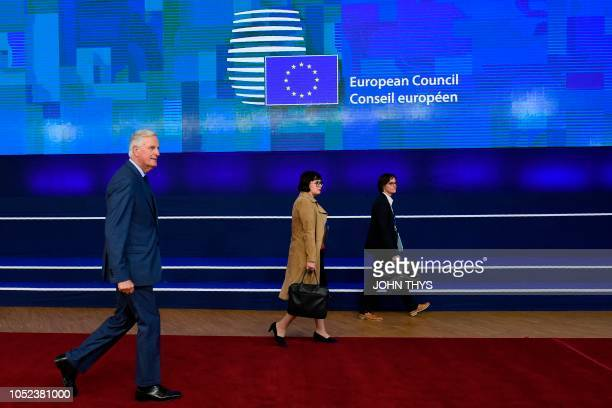 Chief Brexit negotiator Michel Barnier walks with officials upon his arrival at the European Council in Brussels on October 17 2018 British Prime...