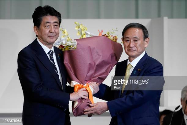 Chief Cabinet Secretary Yoshihide Suga presents flowers to Japan's Prime Minister Shinzo Abe after Suga was elected as new head of Japan's ruling...