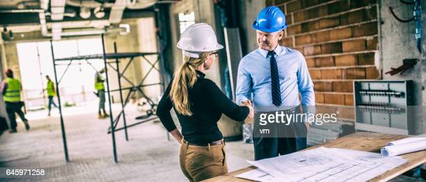 Chief constructor and female architect shaking hands on construction site