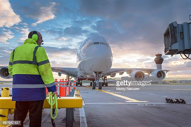 Chief engineer watching A380 aircraft arrive at stand in airport