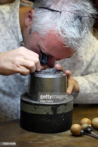 Chief engraver Gordon Summers looks at a cast for the new coin to commemorate the christening of HRH Prince George of Cambridge at The Royal Mint on...