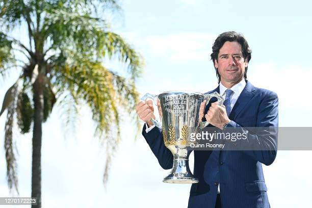 Chief Executive Gillon McLachlan poses with the Premiership Trophy during a press conference announcing to media from the Queensland Quarantine Hub...