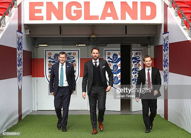 Chief Executive Martin Glenn and FA Technical Director Dan Ashworth walk alongside Gareth Southgate as he is unveiled as the new England manager at...