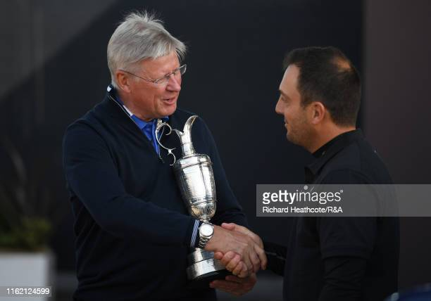 A chief executive Martin Slumbers receives the Claret Jug from 2018 Champion Francesco Molinari of Italy prior to the 148th Open Championship held on...