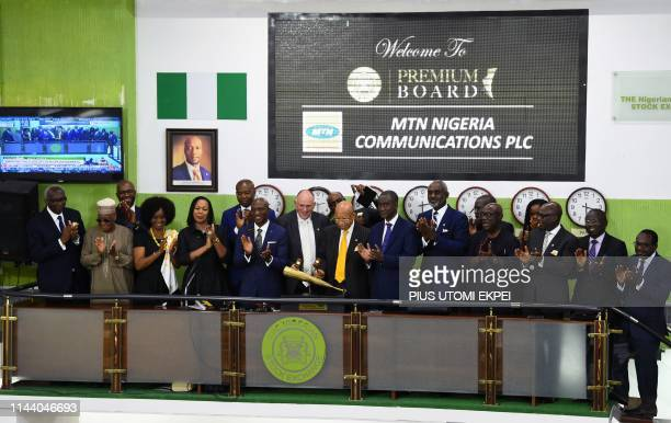 Chief executive of MTN Nigeria Ferdi Moolman and chairman of board Pascal Dozie sound the closing gong flanked by other executives of the board...