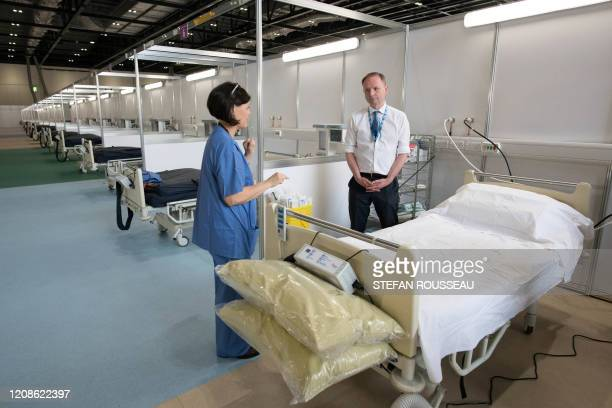 Chief Executive of the National Health Service Simon Stevens chats with a staff member during a visit to the ExCel centre in London on March 30 which...